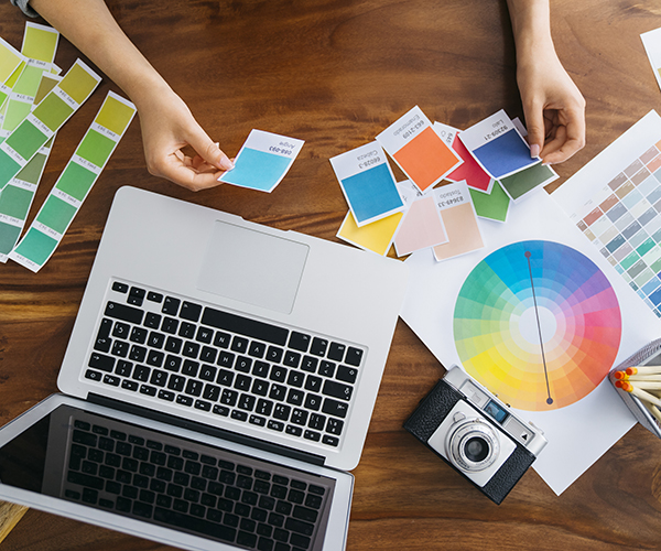 Graphic designer going over Pantone Swatches while using laptop